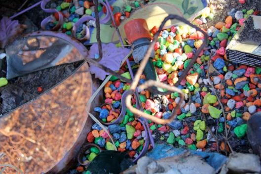 Rainbow aquarium gravel, hose bits and broken mirror, stark against the golden summer landscape of dry grass, grey-green gums.