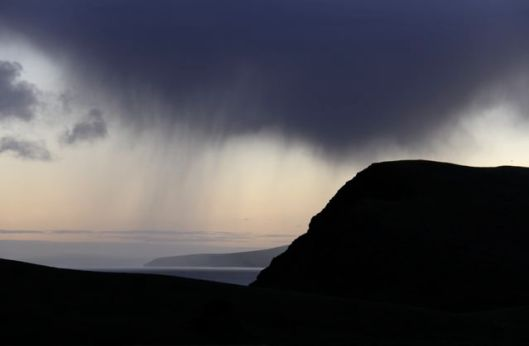 A dawn shower rolls over Second Valley's cliffs on the first day of planting.